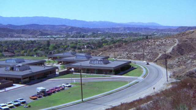 high angle down of industrial complex. buildings could also work for technical or trade school or community college campus. could be  minimum security prison. desert and mountains in bg. camera follows yellow corvette. - prison education stock videos & royalty-free footage
