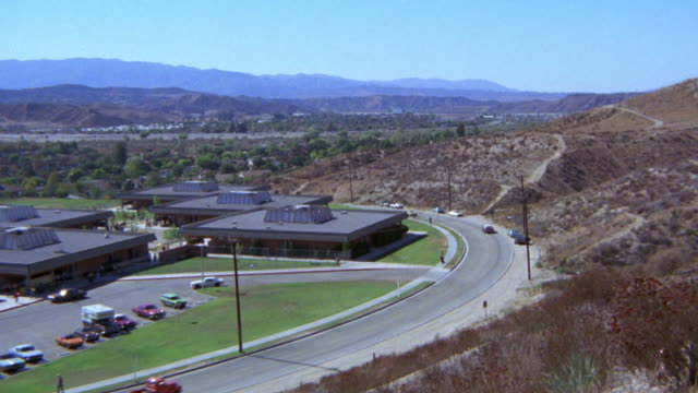 high angle down of industrial complex. buildings could also work for technical or trade school or community college campus. could be  minimum security prison. desert and mountains in bg. camera follows yellow corvette into parking lot. football field with - prison education stock videos & royalty-free footage