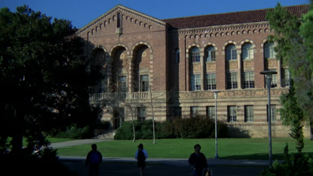ZOOM IN ON MOORE HALL BUILDING ON UCLA CAMPUS. RED BRICK BUILDING. COULD BE HIGH SCHOOL. STUDENTS WALK OUTSIDE ON TREE LINED PATH. CAMERA ZOOMS IN TO SECOND FLOOR WINDOW.