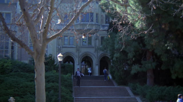 MEDIUM ANGLE OF GRAY STONE BUILDING ON UCLA CAMPUS. COULD BE ACKERMANN OR KERKHOFF.  COULD BE COLLEGE, UNIVERSITY, LIBRARY, OR ADMINISTRATION BUILDING. STUDENTS WALK AROUND AND UP STAIRS. PINE TREES.