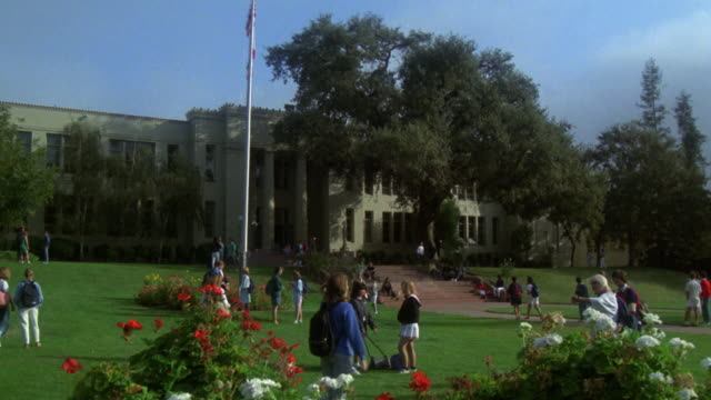 WIDE ANGLE OF HIGH SCHOOL. TEENAGERS OR STUDENTS  STAND ON LAWN OUT FRONT NEAR FLOWER BEDS, FLAG POLE, AND STAIRS.  ROSES. OAK TREE. MATCHES OTHER ANGLE: 1241-F