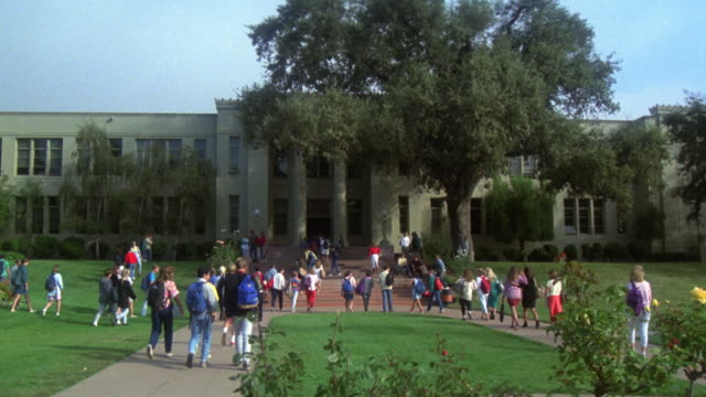 WIDE ANGLE OF HIGH SCHOOL. TEENAGERS STAND OUTSIDE ON LAWN NEAR OAK TREE, STAIRS, AND ROSE BUSHES. MATCHES OTHER ANGLE: 1241-A
