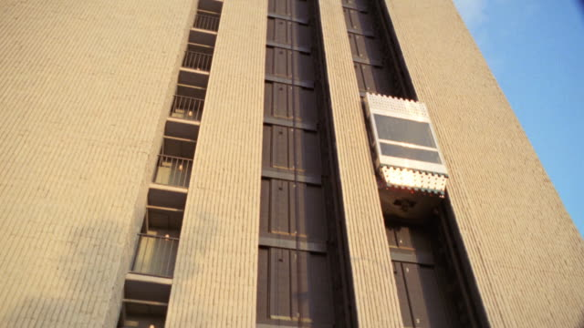 UP ANGLE OF EXTERIOR OF BUILDING WITH EXPOSED ELEVATORS. ELEVATOR ON RIGHT MOVES FROM BOTTOM FLOOR TO TOP FLOOR.