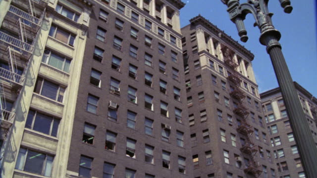 up angle of twelve story brownstone apartment building with fire escapes. pan down to x-rated theater. adult entertainments. - x rated stock videos & royalty-free footage