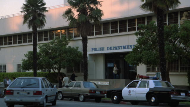 MEDIUM ANGLE OF POLICE DEPARTMENT PRECINCT STATION HEADQUARTERS. NON DESCRIPT WITH BLACK AND WHITE POLICE CARS PARKED OUT FRONT BUILDING IS 2 STORY CEMENT. PALM TREE VISIBLE. LOTS OF ACTIVITY.MATCHING NX 1334-G WITH OTHER DX SHOTS MATCHES R83-8.