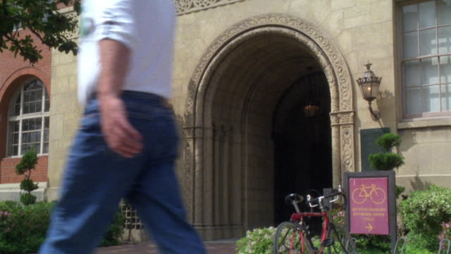"""pan down of  """"science hall"""", lecture hall or classroom building on university college campus. students enter and exit. students dressed in short pants and short-sleeved shirts. see red bike outside of university building. red brick romanesque style archit - short sleeved stock videos & royalty-free footage"""