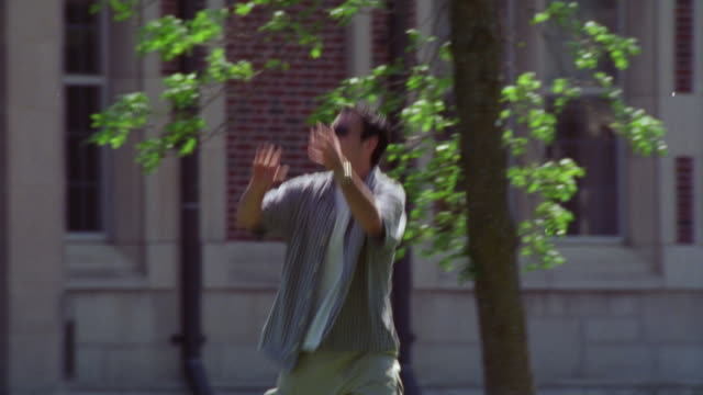 medium angle of college aged men tossing a football back and forth. see light green frisbee also thrown back and forth. sunny day. men dressed in short-sleeved button down shirts. see brick building in bg. could be college building. see green leaves of tr - short sleeved stock videos & royalty-free footage