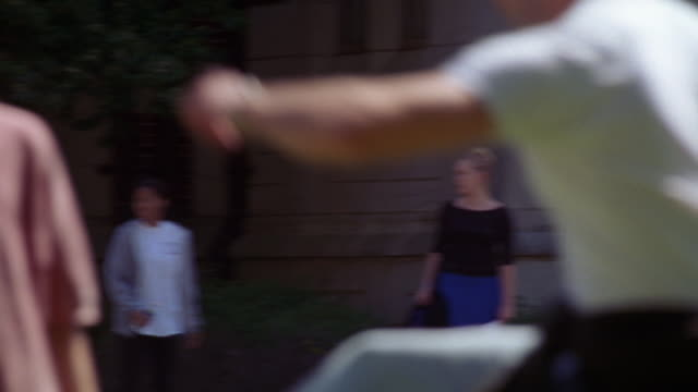 medium angle of college aged men tossing a football back and forth. see man jumping to catch the frisbee. see light green frisbee also thrown back and forth. sunny day. men dressed in short-sleeved button down shirts. see brick building in bg. could be co - short sleeved stock videos & royalty-free footage