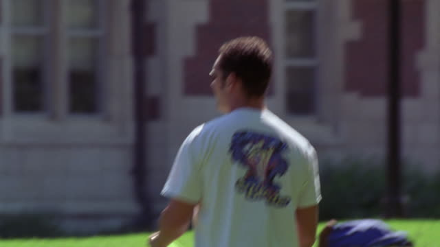 medium angle of college aged man try to catch green frisbee. sunny day. men dressed in short-sleeved shirts. see brick building in bg. could be college building. see green leaves of tree. men also play hackey sack on green grass. see backpacks lying on gr - short sleeved stock videos & royalty-free footage