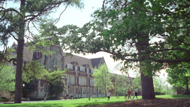 wide angle of large green leafy trees. see  college aged men playing frisbee on green lawn. sunny day. men dressed in short-sleeved shirts. see gothic style limestone masonry multi-story building in bg. could be used for college campus building. agnes sco - short sleeved stock videos & royalty-free footage