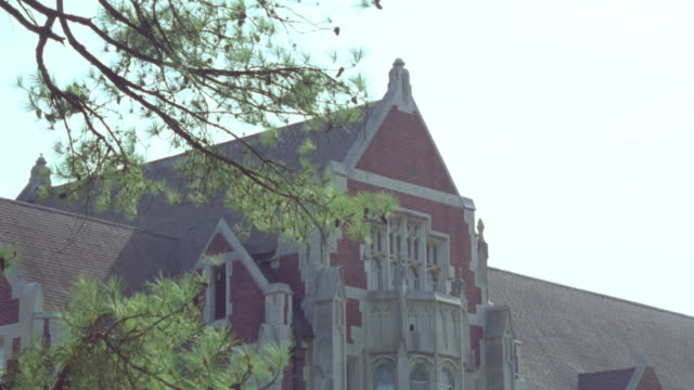 PAN DOWN FROM ROOF PEAK OF GOTHIC-STYLE BRICK BUILDING TO MEN'S COLLEGE STUDENTS WEARING BACKPACKS WALKING ACROSS LAWN OF CAMPUS. BUILDING COULD BE LECTURE HALLS, FACULTY OFFICES OR COLLEGE ADMINISTRATION BUILDING. GREEN TREES IN FRONT OF MULTI-STORY. BUI