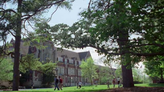 WIDE ANGLE OF GOTHIC STYLE BRICK BUILDING. COLLEGE STUDENTS PLAYING SPORTS. THROWING FRISBEE AND FOOTBALL ON GRASS LAWN. COULD BE PRIVATE ACADEMY SCHOOL OR INSTITUTION. ACTUAL LOCATION IS AGNES SCOTT COLLEGE.