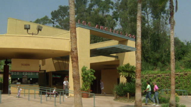 """stockvideo's en b-roll-footage met medium angle of los angeles zoo entrance with  """"los angeles zoo"""" sign across ticket office. trees near entrance. people walking towards entrance and ticket office. children and families. - westelijke verenigde staten"""