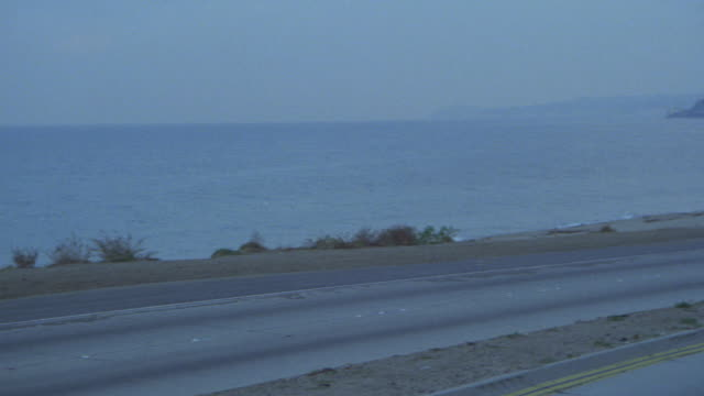 pan left to right to mercedes car with top down driving along beach. pacific coast highway. malibu. - route 001 stock videos & royalty-free footage