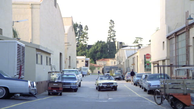 wide angle establish studio street between sound stages. man drives up to in mercedes 450sl car and enters. movie studio lots. - movie studio stock videos and b-roll footage