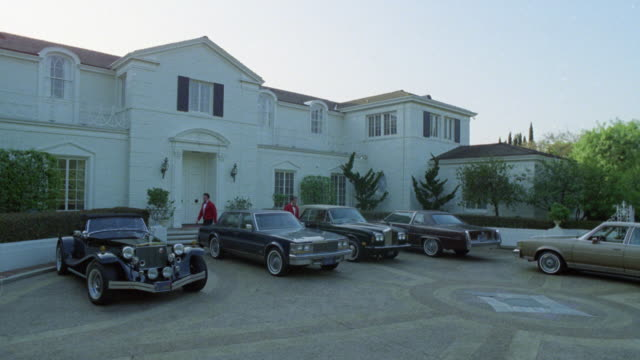 vídeos de stock e filmes b-roll de wide angle of white, two-story mansion with valets in red jackets, and luxury cars in parked in front. cars include rolls royce, stutz bearcat,  cadillacs. neg cut. could be used for party, celebration. beverly hills. bel-air. upper class. - beverly hills