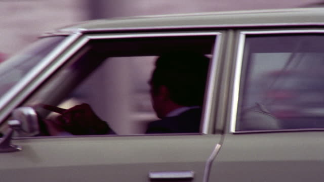 vidéos et rushes de city      shooting side angle    across street traffic to est city street commercial area with stores storefronts light city traffic few pedestrians some people on bicycles / camera pans r-l to follow green 1970's four door car with two men      away from - santa monica