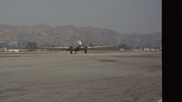 "plane ( dc-3 )  taxies to camera and to right see ""sydon"" painted on plane see sign that says ""sydon terminal"" (r153-3 through r153-5 match) - 1975年点の映像素材/bロール"