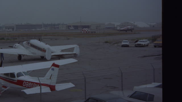 est    small airport field    see small cessna and twin engine planes parked on ramp see commercial airplane taxing down runway l-r air strip   los angeles van nuys airport (r153-3 through r153-5 match) - flygfält bildbanksvideor och videomaterial från bakom kulisserna