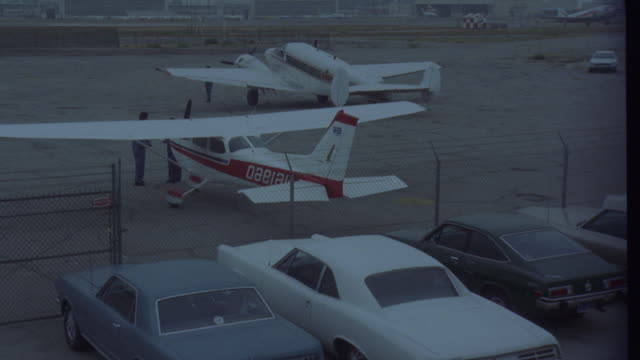 est    small airport field    see small cessna and twin engine planes parked on ramp see commercial airplane taxing down runway l-r air strip   los angeles airport (r153-3 through r153-5 match) - flygfält bildbanksvideor och videomaterial från bakom kulisserna