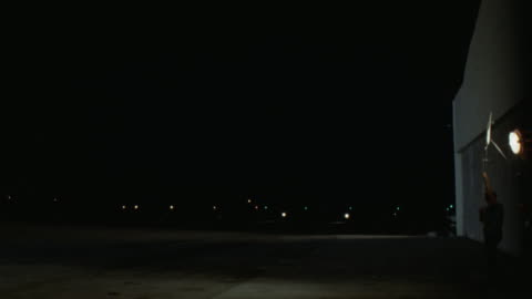 est airport runway see lights of twin engine prop airplane aviation plane  taxies l-r turns then to cam and left to stop see black limo sedan male driver standing next to sedan  man walks to plane never see his face - limousine stock videos & royalty-free footage