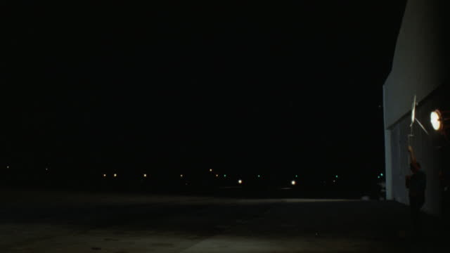 est airport runway see lights of twin engine prop airplane aviation plane  taxies l-r turns then to cam and left to stop see black limo sedan male driver standing next to sedan  man walks to plane never see his face - 1978 stock videos and b-roll footage