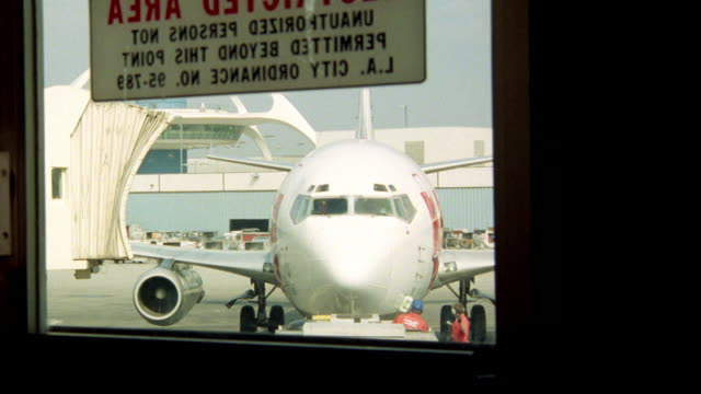 "pov from lobby at airport to 737 est  door window with sign ""restricted area unauthorized person not permitted beyond this point l.a. city ordinance no. 95-789"" see lax restaurant building in bg see commercial airliner as it taxies up to jet way lax airpl - 1982 stock videos and b-roll footage"