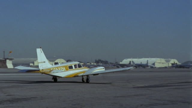 cessna twin engine airplane   taxies r-l on runway    see jet takeoff l-r see yellow pickup truck drive l-r  burbank airport - burbank stock-videos und b-roll-filmmaterial
