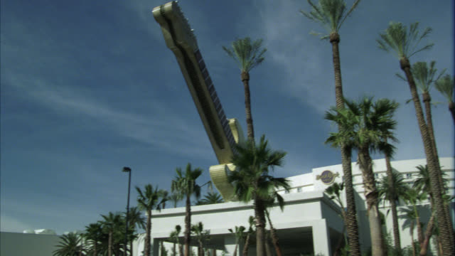 pan down of hard rock hotel. could be casino. multi-story building. palm trees. large model of guitar. cars in parking lot. signs. - ハードロックカフェ点の映像素材/bロール