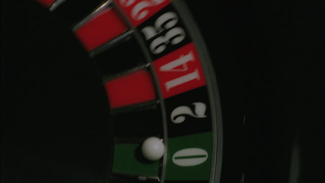 close angle of roulette wheel spinning, ball lands in green zero slot. dealer places marker on winning bet, slides huge stack of chips to player. casinos. gambling. hard rock casino.preview file has been trimmed from master clip 2045-018. for additional f - roulette stock videos & royalty-free footage