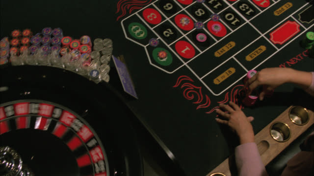 "medium angle of roulette wheel spinning. dealer spins the ball. players make bets on table. ball lands on ""11 black."" casinos. gambling chips. hard rock casino. las vegas.preview file has been trimmed from master clip 2045-018. for additional footage, see - casino stock-videos und b-roll-filmmaterial"