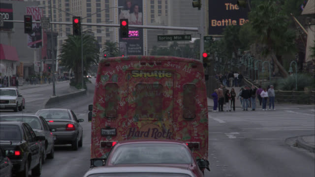 medium angle of hard rock cafe shuttle bus, cars stopping in traffic, as seen from car pulling up behind the vehicles. las vegas strip at spring mtn road.preview file has been trimmed from master clip 2045-034. for additional footage, see clips 2045-921 t - ハードロックカフェ点の映像素材/bロール