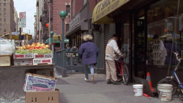 looking down sidewalk. shops on right. subway entrance in bg. woman in purple jacket runs in from behind camera down subway entrance. - anno 1994 video stock e b–roll
