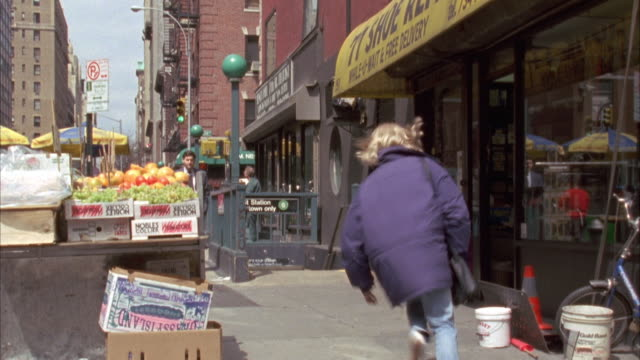 looking down sidewalk. shops on right. subway entrance in bg. woman in purple jacket runs in from left then down subway entrance. - 1994 stock videos and b-roll footage