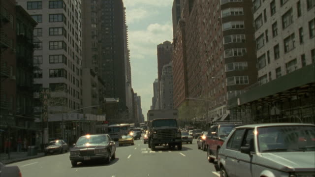 back plate. traffic following camera. buildings on either side of street. - anno 1994 video stock e b–roll