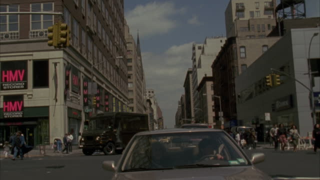 back plate. traffic following camera. buildings on either side of street. camera comes to a stop at end of shot. - anno 1994 video stock e b–roll
