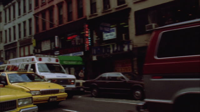 back plate. traffic following behind camera. camera turns right onto side street. cars parked on either side. pedestrians walking across street in bg. - anno 1994 video stock e b–roll