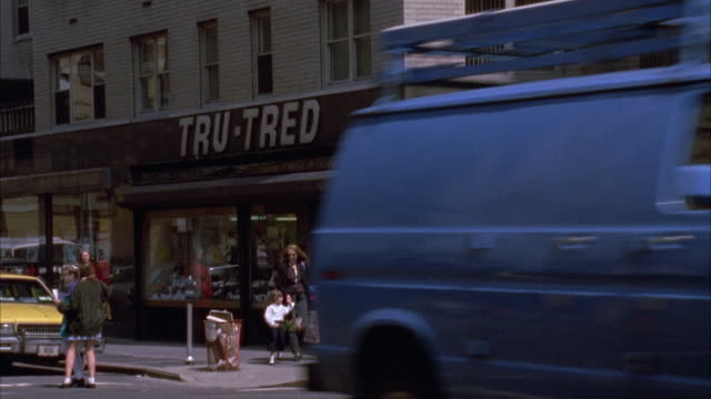 street corner with black and white building in bg. traffic passes from r-l in fg. people walking in front of building. name on building says tru-tred. - anno 1994 video stock e b–roll