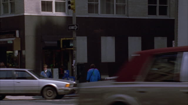 street corner with black and white building in bg. traffic passes from r-l in fg. people walking in front of building. - anno 1994 video stock e b–roll