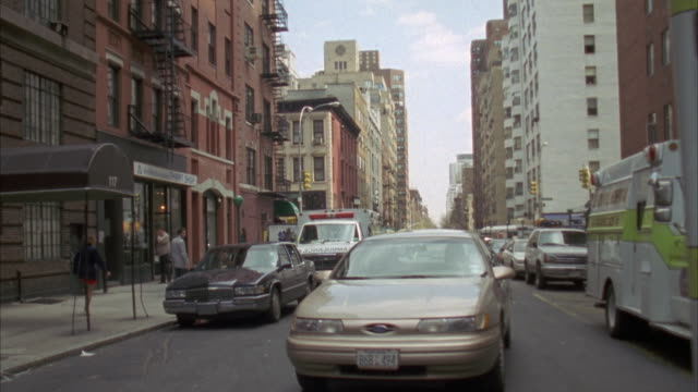 back plate. driving down one way street. cars parked on either side. camera pulls off to right and stops. red car pulls up behind it. - one way stock videos and b-roll footage