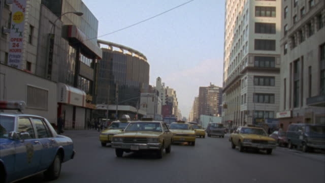back plate. traffic following camera. three lane one way street. buildings on either side of street. - anno 1994 video stock e b–roll