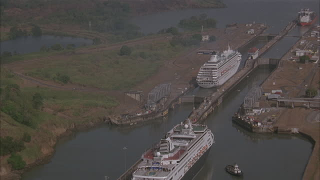 aerial. moving down towards the panama canal to a cruise ship passing the gatun lock. shot lowers and passes by cruise ship. - panama canal stock videos & royalty-free footage