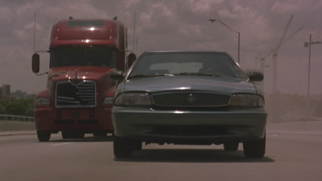 medium angle driving pov of a cadillac sedan on a highway.  could be freeway or interstate.  the sedan is chased by a red eighteen wheeler car transport truck.  the truck crashes into a sedan, causing it to spin out.  the front of the truck has been damag - american interstate stock videos & royalty-free footage