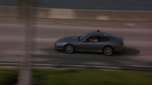 AERIAL OF A FERRARI SPORTS CAR RACING ON A FREEWAY, INTERSTATE OR HIGHWAY NEXT TO A RIVER OR OCEAN. LINED WITH PALM TREES.  THE CAR SWERVES THROUGH THE TRAFFIC.  A MAN HANGS OUT OF THE PASSENGER WINDOW WITH A RIFLE OR GUN.