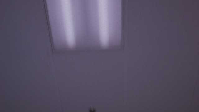 UP ANGLE. CAMERA MOVING WHILE LOOKING UP AT CEILING WITH FLUORESCENT LIGHTS. COULD BE HOSPITAL HALLWAY.