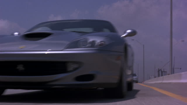 vídeos de stock, filmes e b-roll de up angle tracking pov of a ferrari sports car swerving and racing through traffic on a highway, freeway, or interstate. several police cars chase the ferrari. a helicopter can be seen following from above.  a bridge in the background. - carro esportivo