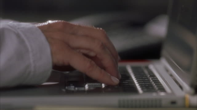 CLOSE ANGLE OF WOMAN'S HANDS TYPING ON BLACK LAPTOP COMPUTER. WOMAN WEARING WHITE LONG SLEEVE.