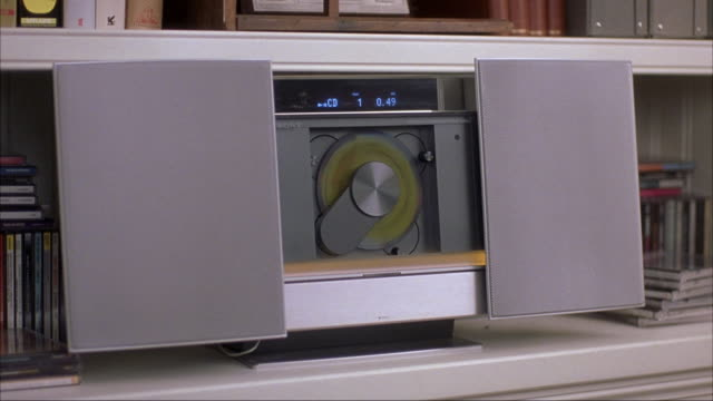medium angle shot of contemporary cd stereo as cd spins toward the viewer on a bookshelf with books and cds surrounding. - compact disc player stock videos & royalty-free footage