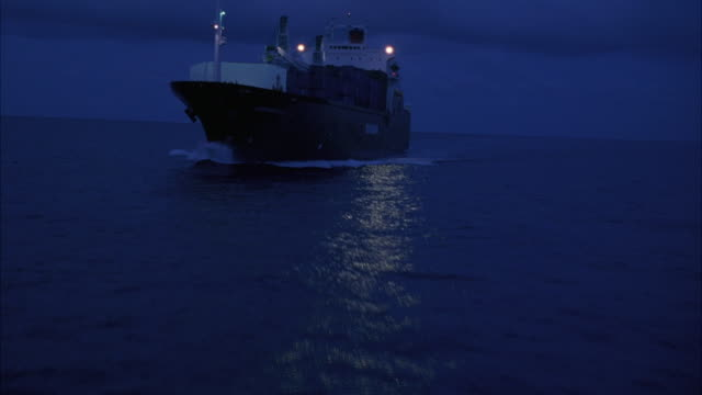 aerial. passing over ocean water at night. passes above freight ship with cargo on deck in middle of ocean. - cargo ship stock videos & royalty-free footage