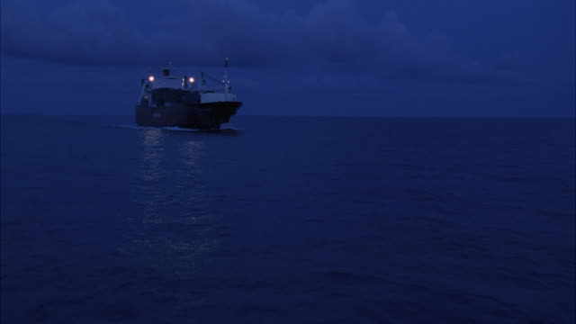 aerial. passing over ocean water at night. passes above freight ship with cargo on deck in middle of ocean. - ship stock videos and b-roll footage